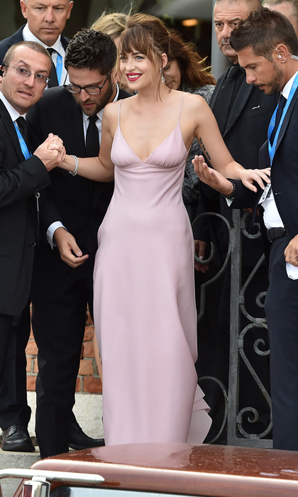 Dakota Johnson dazzled in pale-pink Prada for the premiere of <em>Black Mass</em> in 2015. Her best accessory? The throngs of men who surrounded her to help get the actress safely aboard a water taxi.