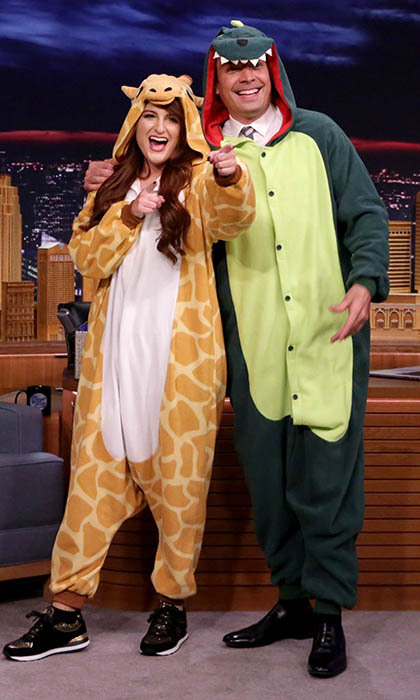 Onesies never looked so cool! Meghan Trainor arrived to the <i>Tonight Show</i> bearing gifts as she presented Jimmy Fallon with his very own dinosaur suit. 