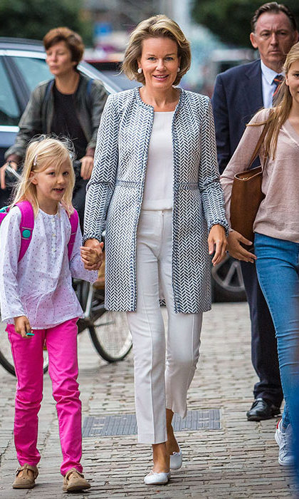 Queen Mathilde did the school run in a blue patterned coat and white tailored cropped trousers.