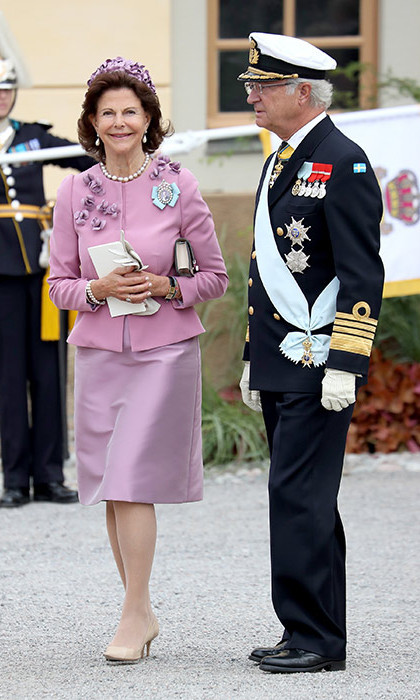 Queen Silvia wore a pink dress and jacket adorned with floral corsages.