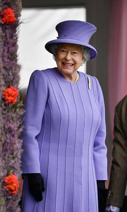 The Queen looks cheerful in a purple coat and matching hat at the 2016 Braemar Highland Gathering.