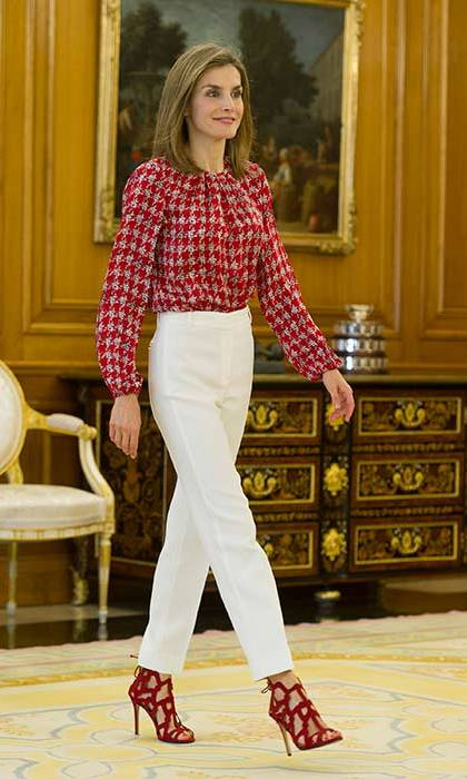 Queen Letizia looks as fashion forward as ever in a red houndstooth blouse and cream trousers, accessorised with amazing strappy red sandals.