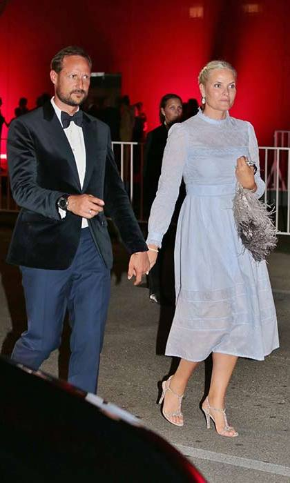 Princess Mette-Marit glammed up for Venice Film Festival in a lilac midi dress with a statement tasselled handbag.