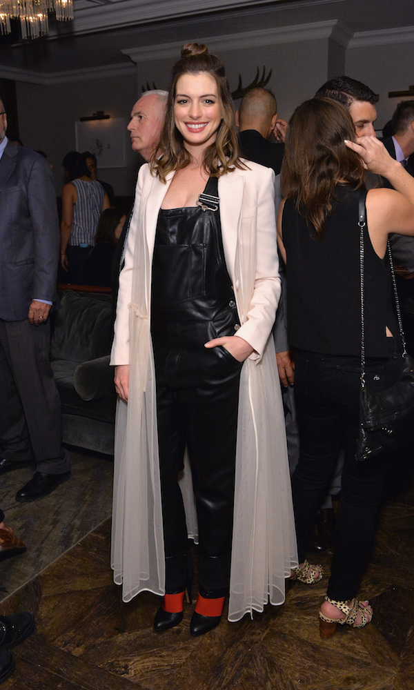 Anne Hathaway traded her embellished cream cocktail dress from the premiere of <em>Colossal</em> for a pair of  Givenchy leather overalls and a chic floor-length coat at Grey Goose Soho House.