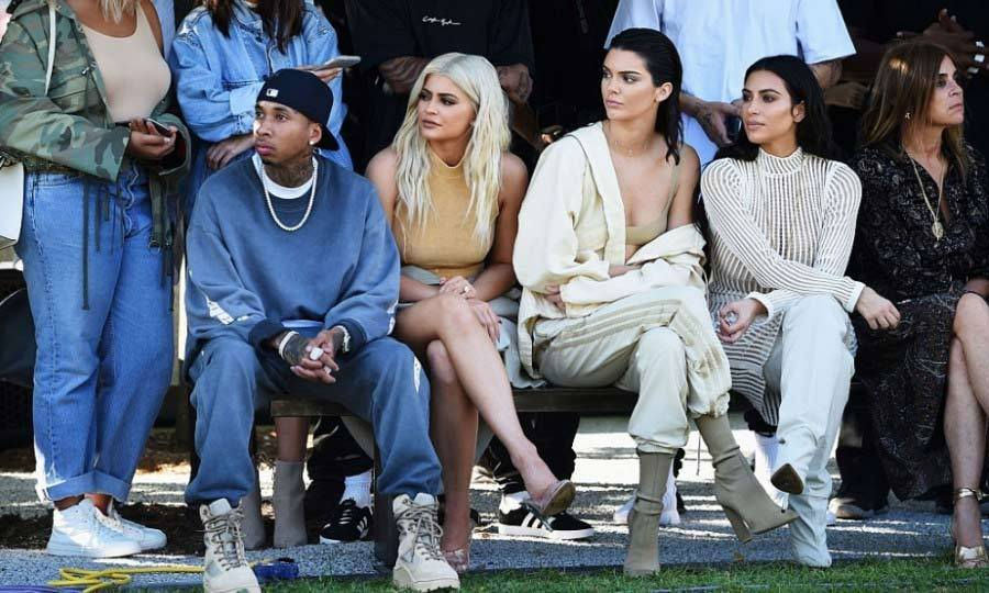 Despite starting late, Kim and her family watched the models including Sofia Richie and Chanel Iman walk as regulars were cast to stand in the middle of the field for the duration of the show.