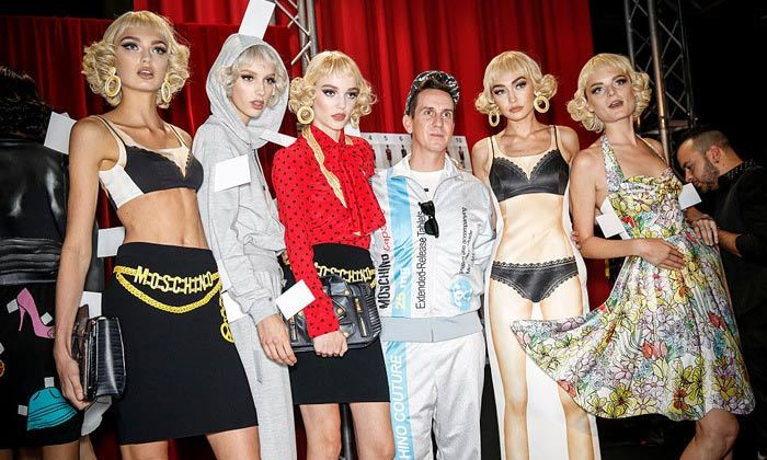 Designer Jeremy Scott sent models down the Moschino runway dressed as paper dolls featuring white fold-down dressing tabs.