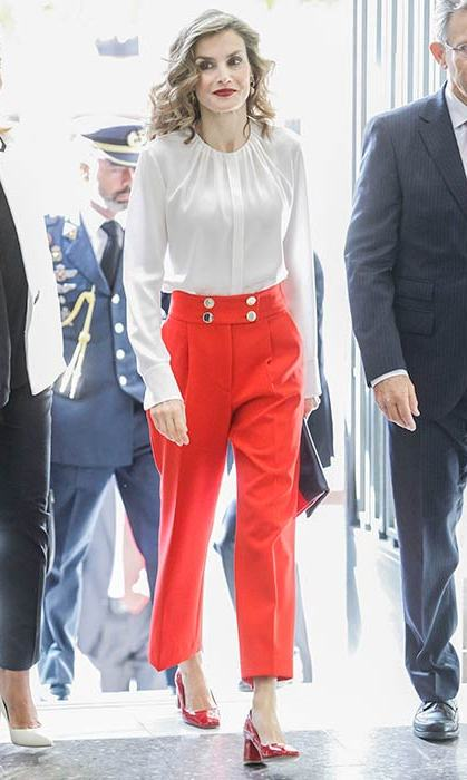 Queen Letizia turned heads in a white blouse and bright red high waisted trousers at the Red Cross headquarters in Madrid.