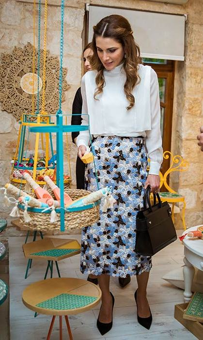 Queen Rania looked elegant in a cream blouse and blue floral midi skirt to tour the Jordan River Foundation.