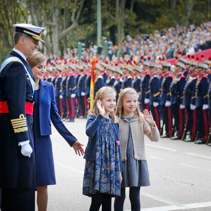 Letizia and Felipe proudly looked on as their daughters waved to well-wishers during Spain's 2015 National Day celebrations. 