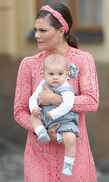 Looking like quite the little gentleman, six-month-old Prince Oscar took in all the action at his cousin Prince Alexander's christening while nestled in his mother's arms. 