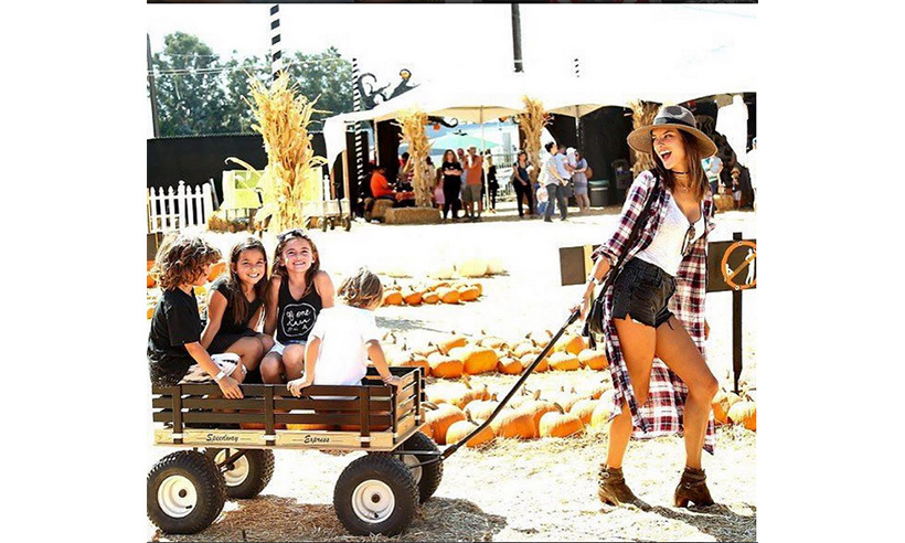 Alessandra Ambrosio is a wagon master at the pumpkin farm.