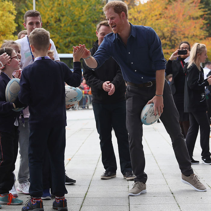Showing off his fun side, Harry gave a high-five to a young boy during a rugby game.