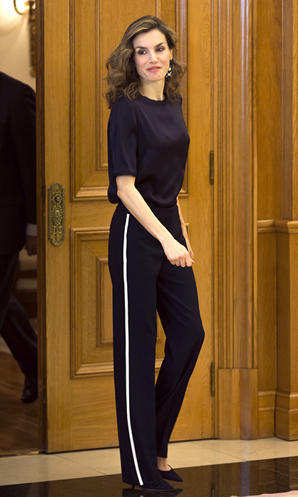 Queen Letizia of Spain kept her look sporty and sleek in black tuxedo pants with a white stripe down the side, a silky black short-sleeve blouse and black pumps for an event at her Madrid home. <br>Photo: © Getty Images