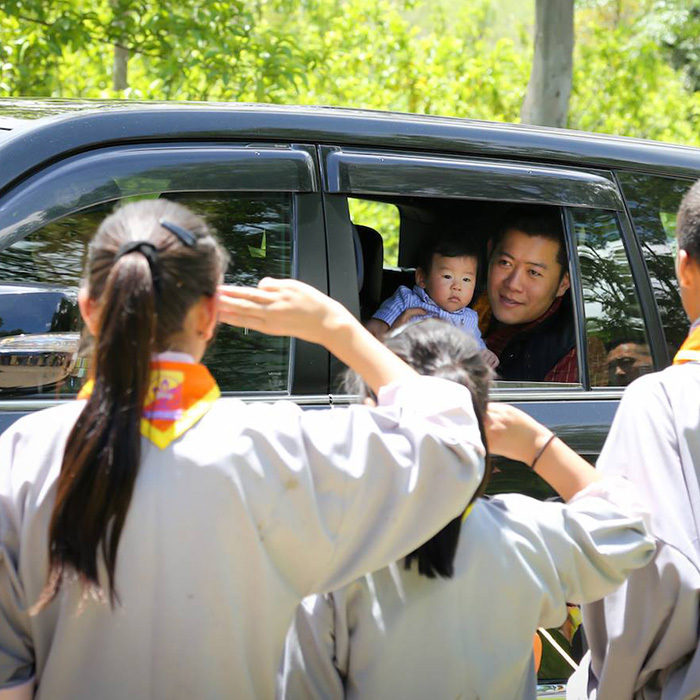 "Here, Jigma says ""Hello!"" to some students while on tour with his parents in Eastern Bhutan. 