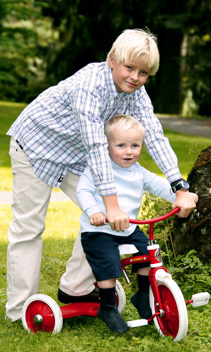 Marius helps his younger brother Sverre Magnus go for a ride in the gardens of  Skaugum Palace. 