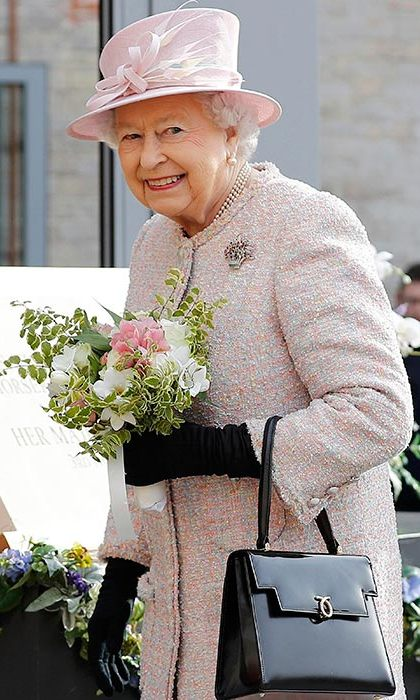 The Queen wore a pretty pink coat and matching hat for a visit to Newmarket.