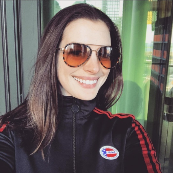 Anne Hathaway cracked a smile and showed off her sticker after casting her vote. 