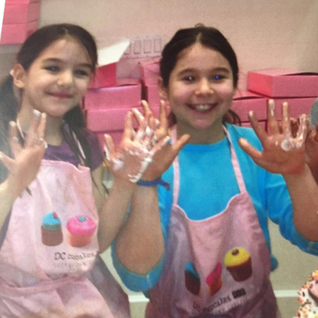 Katie Holmes shared an adorable snap and strong message with this cute photo of daughter Suri and a friend decorating sweet treats at DC Cupcakes.