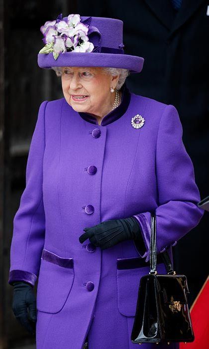 The Queen wore a vibrant purple coat and co-ordinating hat, complete with floral bouquet.