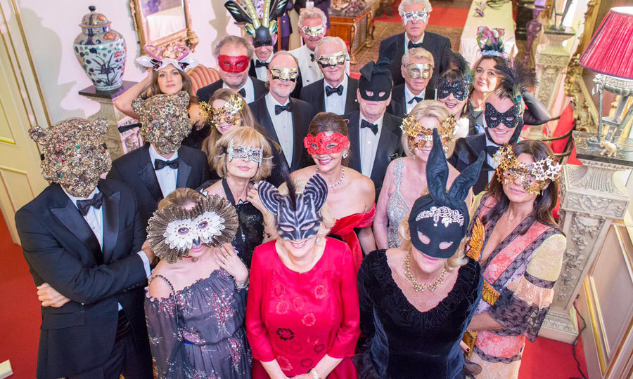 Things got <em>wild</em> for the Duchess of Cornwall (in red)! Prince Charles' wife donned an animal mask alongside supporters of the Elephant Family organization at the charity's Animal Ball.<br>Photo: &copy Twitter