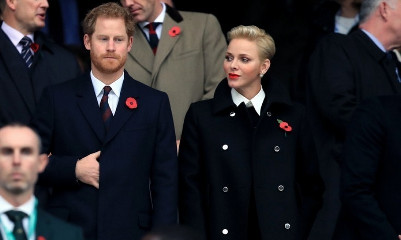 Though some were expecting to see Prince Harry's girlfriend Meghan Markle by his side during the England vs. South Africa rugby match at Twickenham, he was instead joined by Monaco's Princess Charlene. The two cheered on while wearing poppy pins to remember the soldiers who lost their lives in battle.<br>Photo: &copy; PA