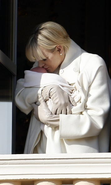 January 2015: Princess Charlene kisses one of her newborn twins during the royal introductions in Monaco. 