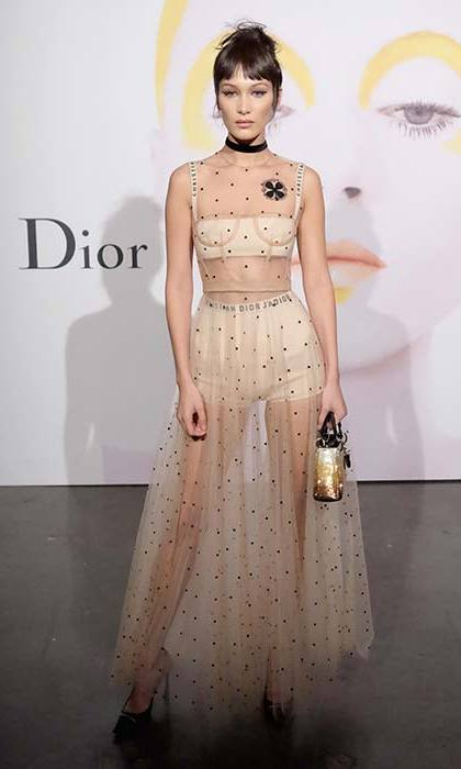 Bella works her signature edgy glamour in a sheer Dior gown with a black choker.