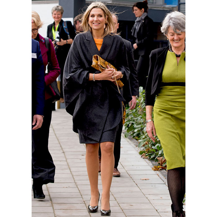 Queen Máxima of the Netherlands looked cozy donning a grey wrap poncho over her vibrant knit top and pencil skirt for an outing to Thomas More College in Rotterdam, where she talked about the development of music education.