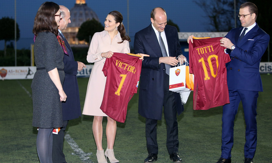"Victoria and her husband Prince Daniel were gifted AS Roma soccer jerseys from AS Roma's general manager Mauro Baldissoni during their visit to the AS Roma soccer club at the St. Peter's Pontifical Oratory. The pair were on hand to see the club's project, ""Calcio Insieme,"" for young individuals with disabilities.
