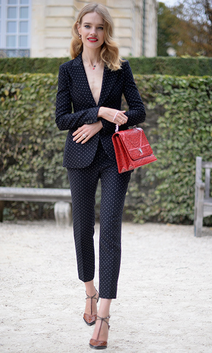 Natalia Vodianova looked trés chic in a trouser suit, which she accessorized with a vibrant red bag, for the Christian Dior show during Paris Fashion Week Womenswear Spring/Summer 2017.