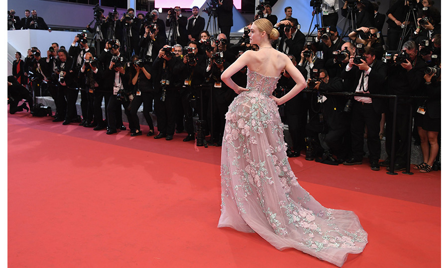 It couldn't have been more of fairytale movie-star moment for Elle Fanning at this year's Cannes Film Festival. The actress skipped her senior prom to stroll the Promenade de la Croisette in a dusty pink Zuhair Murad couture gown dotted with hundreds of rose appliqués. 