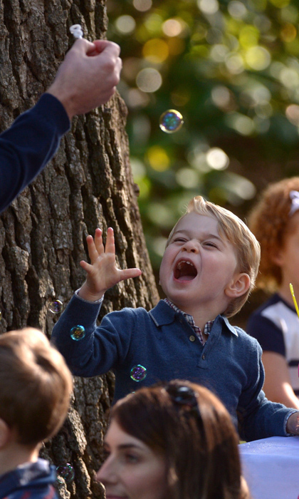 At a children's party in Victoria, George loved catching bubbles with his dad Prince William. 