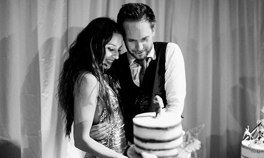The newlyweds cut into their tiered red velvet cake. 