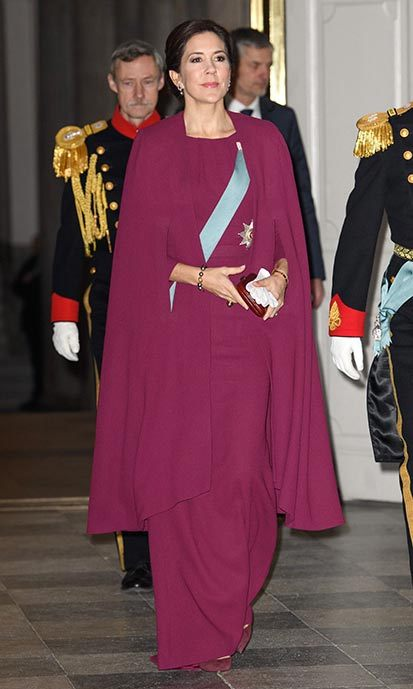Crown Princess Mary looked pretty in purple wearing a full-length gown and matching cape overcoat to a New Year reception at Christiansborg Palace in Copenhagen.