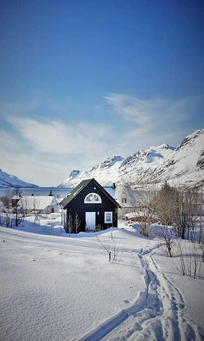 <h3>STAY</h3><p>In snow-dusted Ersfjordbotn (above) – a small village just outside Tromsø – sits the cosiest of cabins: a peaceful, wood-clad den with two bedrooms, low-energy lighting and a dramatic craggy backdrop.</p><p>Decked out in neutral colours, the cabin's interior gives a firm nod to Scandinavian style and has all of the creature comforts you could wish for. Curl up beside the half-moon window and watch as the light shifts across the deep sapphire sky, or wander down to the fjord to spot killer whales as they glifde through the cool Norwegian waters. </p>