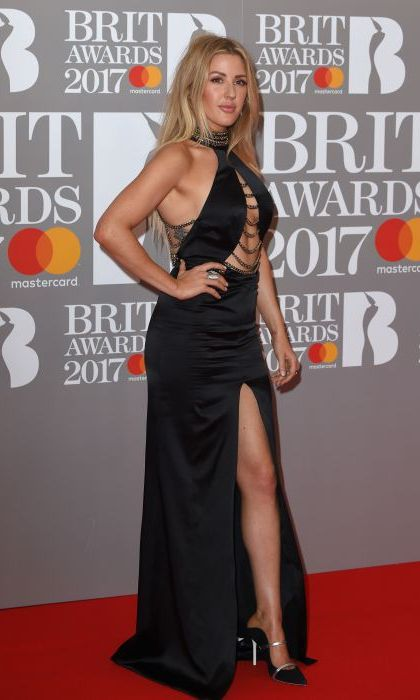 Ellie Goulding wowed in this daring black gown which featured a dramatic open neckline and thigh high split. Ellie paired the chain embellished gown with co-ordinating black and silver pointed heels and wore her blonde hair down and loose. 