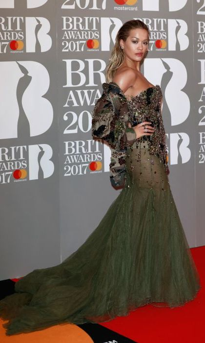 Rita Ora looked stunning in this khaki sheer embellished gown, with slicked back hair and metallic makeup to complement the look. 