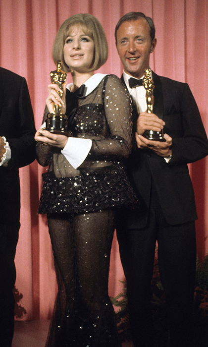 "<strong>Barbra Streisand, 1969</strong><br><br>Not only did the <em>Funny Girl</em> star shockingly tie for Best Actress (with Katharine Hepburn, whose director Anthony Harvey, pictured here, accepted on her behalf), but Barbra also caused quite the stir with what she wore: a sheer sequinned bell-bottomed pantsuit by Arnold Scaasi. The actress and singer wrote years later: ""I had no idea when I wore it to receive the Academy Award that the outfit would become see-through under the lights!""<br><br><strong>David Lee @HelloCanada</strong>"