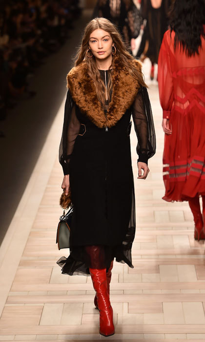 Gigi Hadid worked the runway modelling red boots and a black ensemble with fur stole at the Fendi fashion show in Milan.
