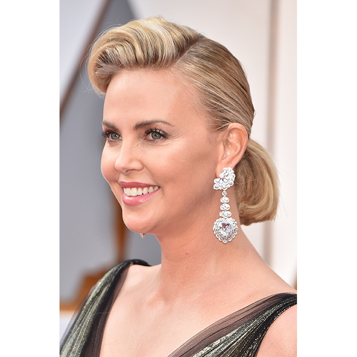 Charlize Theron accessorized her beautiful gold lamé Dior gown with out-of-this-world pear-shaped diamond earrings from Chopard. Set in white gold, each earring weighed in at a whopping 60 carats. Less prominent though no less stunning was the actress's 12-carat ring, also from Chopard. 