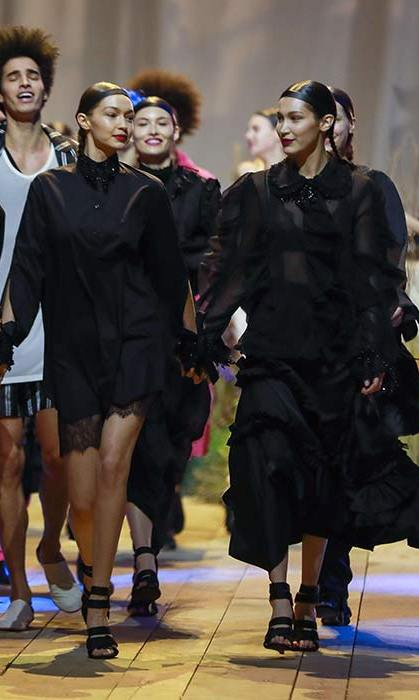 Gigi Hadid and Bella Hadid held hands as they walked the runway at the H&M Paris Fashion Week show.