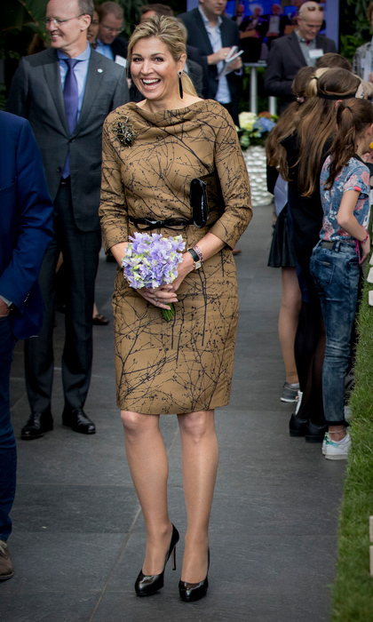 Queen Maxima wore a printed, tan-coloured dress that featured a cowl neckline to visit the horticultural company Koppert Cress, which specializes in a variety of edible plants and flowers that are used by national and international chefs, restaurants and hotels.