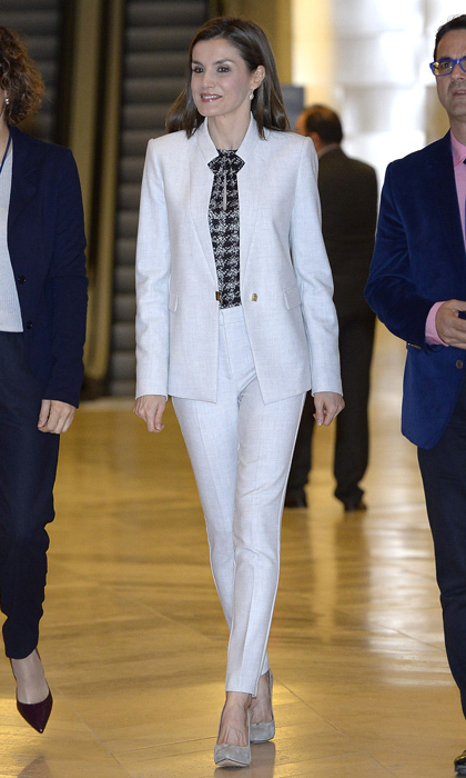 Queen Letizia of Spain was a vision in white stepping out wearing high-waisted BOSS trousers and a BOSS fitted blazer with metal detail to a 2017 Rare Diseases Day event held at El Prado Museum in Madrid, Spain.
