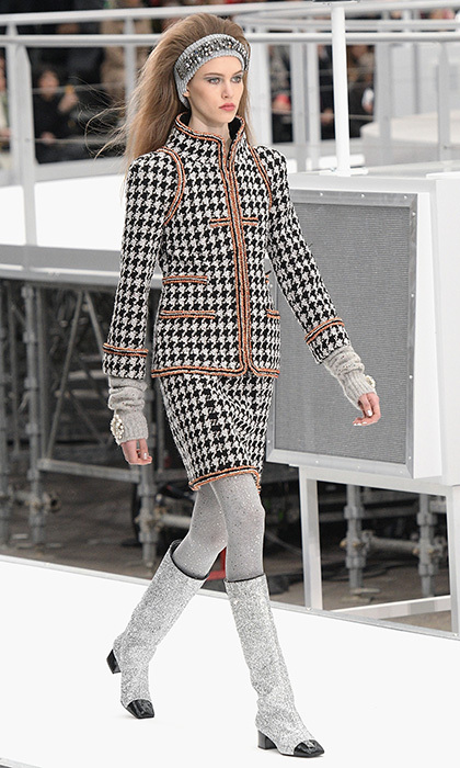 <p><strong>Paris Fashion Week</strong></p><p>Chanel's iconic heritage tweed is reimagined with a sixties-inspired hounds tooth print, a look that would be ideal for Kate to wear to an afternoon luncheon. And yes, we secretly hope she would swap her classic pumps for a pair of these glittering boots!</p><p>Photo: © Getty Images</p>