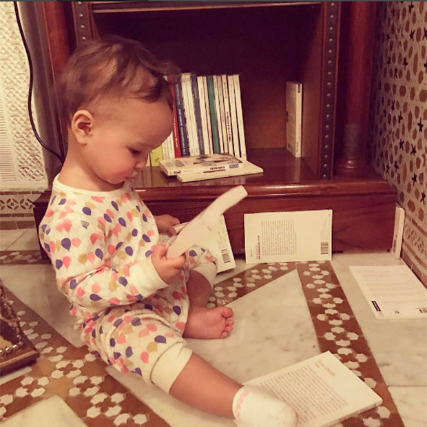 "The 11-month-old got in some ""Light vacation reading"" while visiting Morocco with her famous parents. The family of three headed to North Africa with their close friend, and Chrissy's hairstylist, Jen Atkin.  