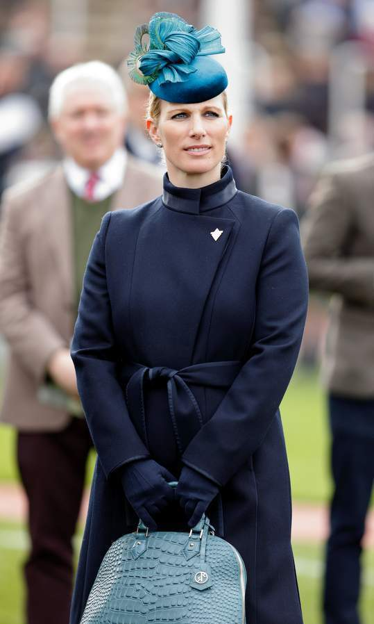 Queen Elizabeth's granddaughter Zara Tindall matched her navy coat with a blue hat and purse at the Cheltenham festival in England.