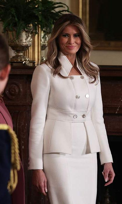 <p>Melania Trump looked elegant in a bespoke Karl Lagerfeld Couture skirt suit for her first official appearance at the White House on Wednesday. The white cashmere suit featured a double breasted jacket with statement collar and silver button detailing, and a matching pencil skirt.</p><p>The First Lady, who had previously been rumoured to wear an outfit from the designer at the inauguration, styled the ensemble with white court shoes and wore her hair down in loose waves.</p><p>Photo: &copy; Getty Images</p>