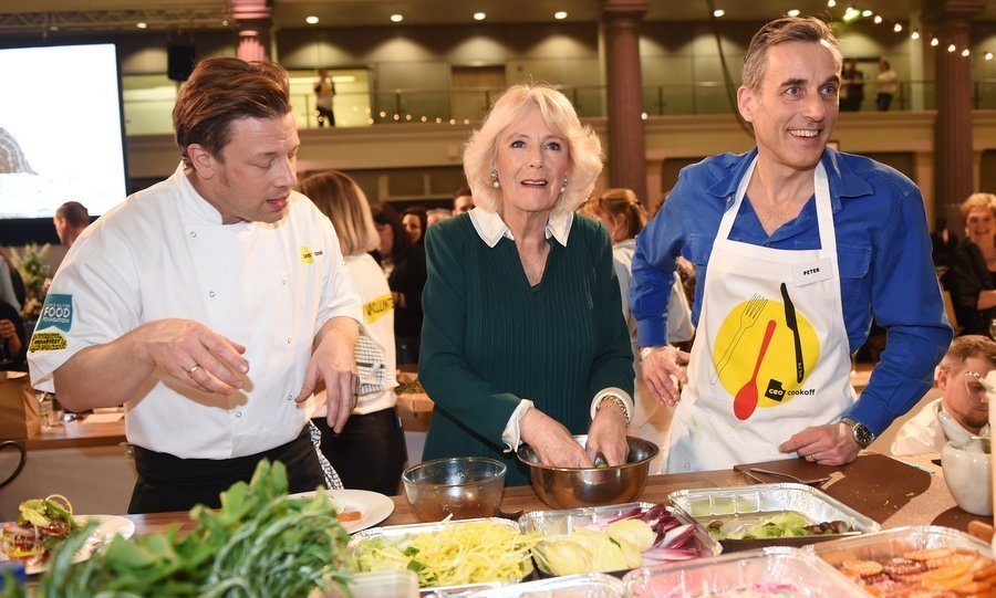 What's cookin'? The Duchess of Cornwall seemed to have the answer as she teamed up with celebrity chef Jamie Oliver, left, and CEO of Lucozade Ribena Suntory Peter Harding at the CEO Cook Off in support of UK Harvest and the Jamie Oliver Food Foundation in London on Mar. 21.