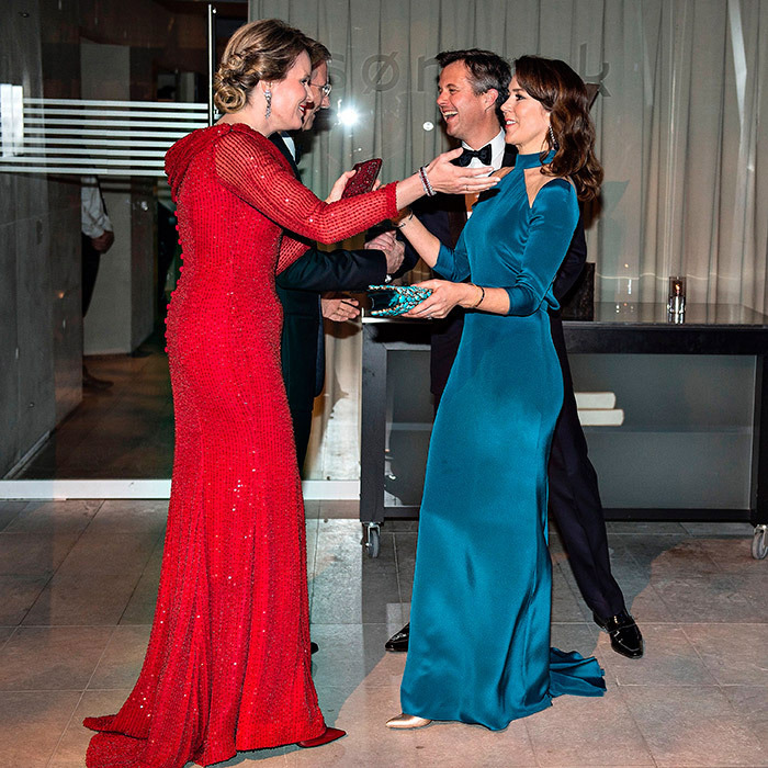 Fancy meeting you here! Queen Mathilde of Belgium, left, and Crown Princess Mary of Denmark, right, said hello at a reception in Copenhagen on Mar. 29.