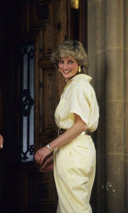 Princess Diana smiling while wearing a yellow outfit.